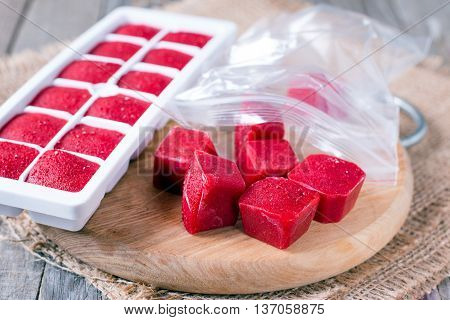 Cubes berries  in cruets on a wooden board