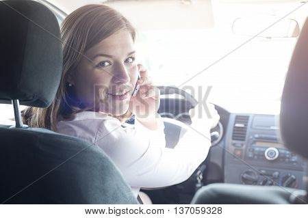 Happy Attractive woman holding steering wheel and talking on the phone in car