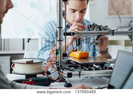 Students sitting at the laboratory desk and using a 3D printer for prototyping