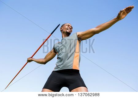 Low angle view of happy athlete about to throw a javelin in the stadium