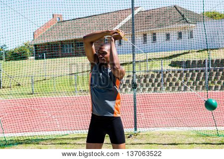 Determined athlete performing a hammer throw in stadium