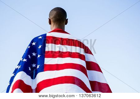 Rear view of athlete wrapped in american flag