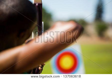 Close-up of athlete practicing archery in stadium