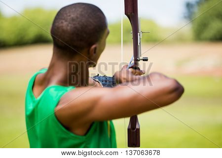 Rear view of athlete practicing archery in stadium
