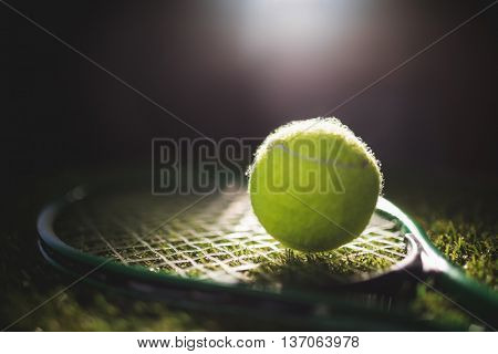 Close up of tennis ball with racket on grass