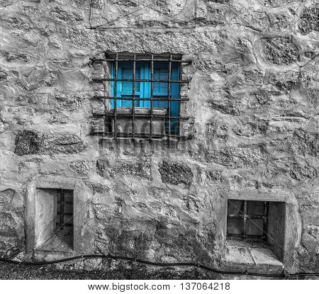 selective desaturation of a blue window in a rustic wall in Sardinia Italy