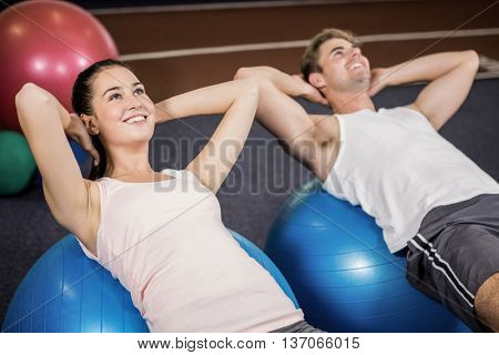 Man and woman doing abdominal crunches on fitness ball at gym