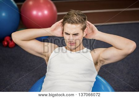 Man working out on a fitness ball at gym