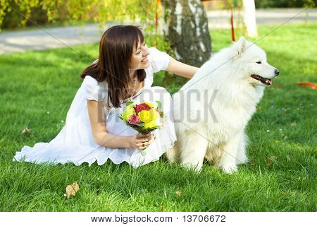 Bride with dog Samoyed sitting on the grass poster