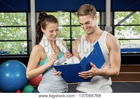 Woman talking to her trainer after a workout at gym