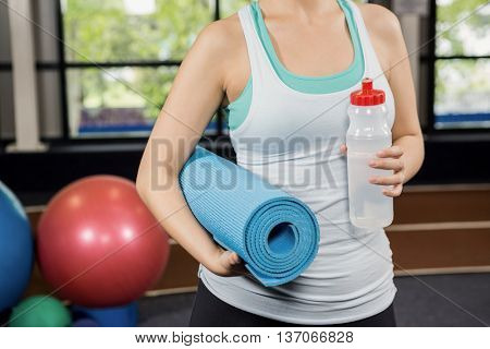 Mid-section of woman holding exercise mat and water bottle at gym