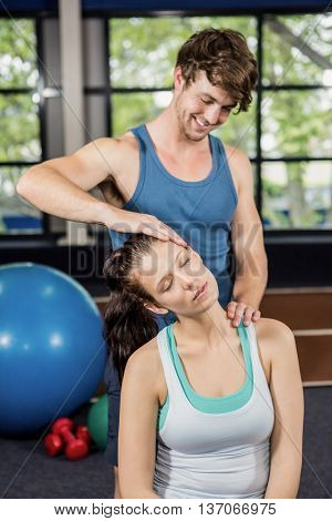 Trainer assisting woman with neck exercise at gym
