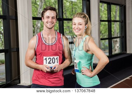 Portrait of happy man and woman listening to music and using phone at gym