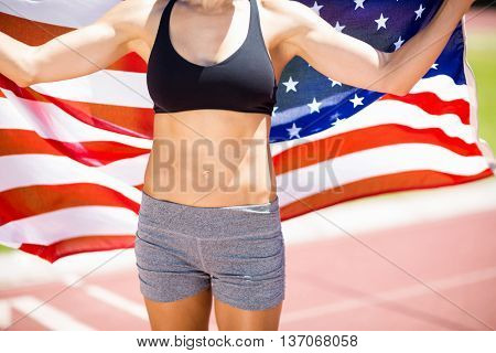 Mid section of female athlete holding up american flag on running track in stadium
