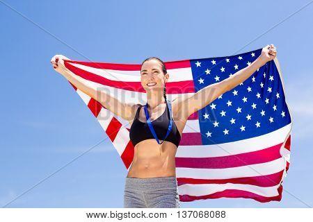 Happy female athlete holding up american flag in stadium