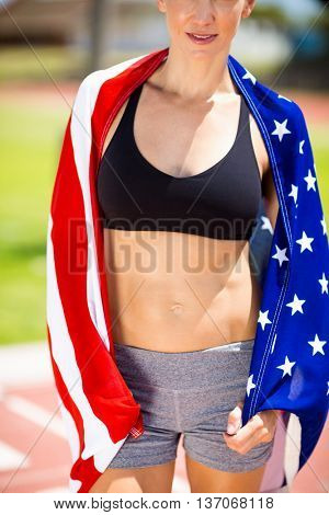 Mid section of female athlete wrapped in american flag on running track in stadium