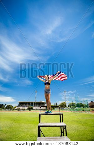 Happy female athlete holding up american flag in stadium