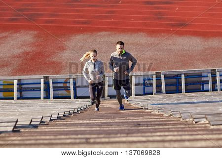 fitness, sport, exercising and lifestyle concept - couple of man and woman running upstairs on stadium