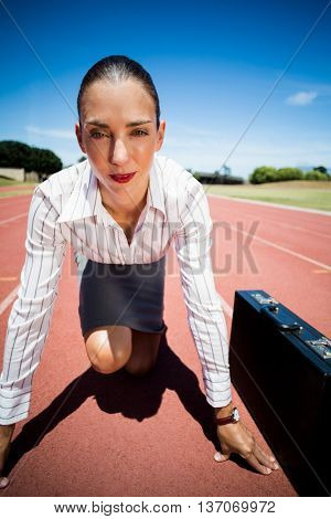 Portrait of confident businesswoman with briefcase in ready to run position on running track