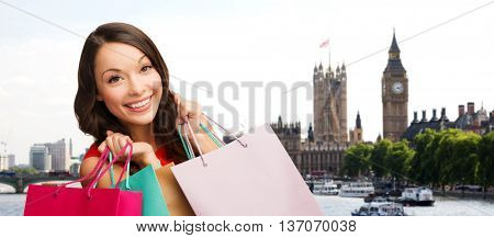 people, holidays, tourism, travel and sale concept - young happy woman with shopping bags over london city background