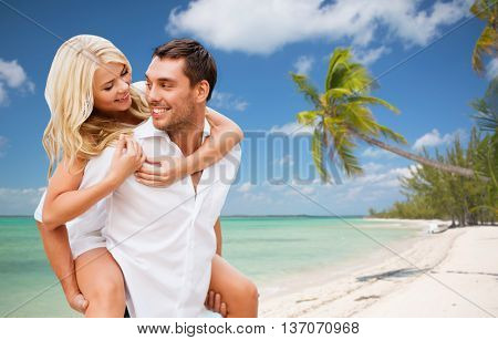 travel, tourism, summer holidays, vacation and love concept - happy couple having fun over exotic tropical beach with palm trees background