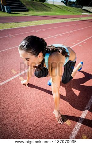 Female athlete in ready to run position on running track