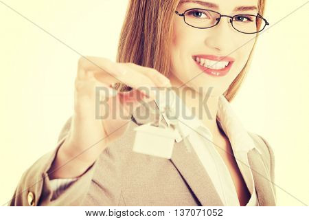 Caucasian business woman holds home keys.