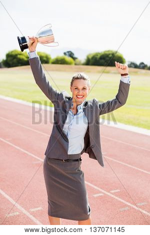 Portrait of happy businesswoman holding up a trophy on running track