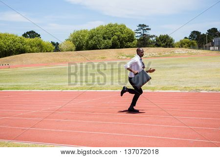 Businessman with briefcase running on a running track