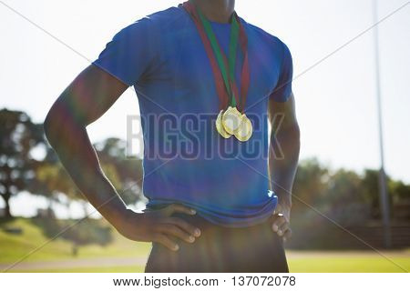 Mid section of athlete posing with gold medal after victory on running track
