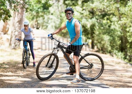 A Couple riding bike on the wood