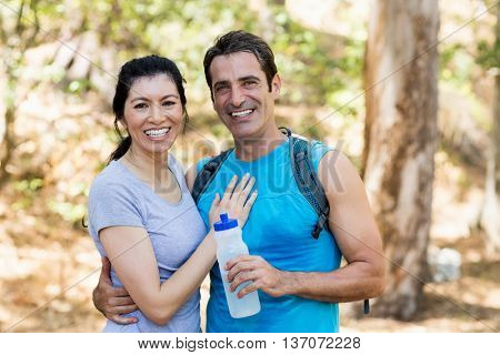 Portrait of a couple smiling and holding each other on the wood