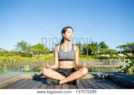 Woman sitting in yoga pose at park