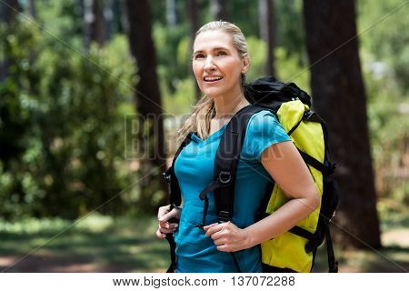 Woman looking up and posing with a backpack on the wood