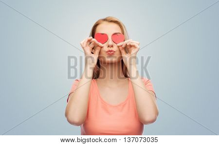 love, romance, valentines day and people concept - smiling young woman or teenage girl with red heart shapes on eyes over gray background