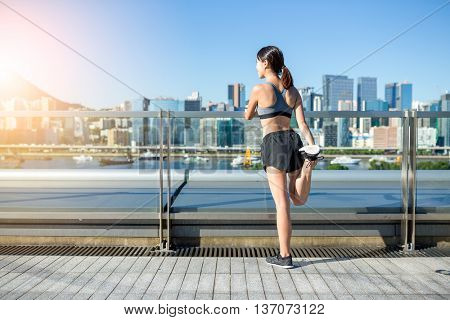 The back view of woman stretching legs in city