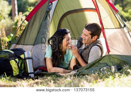 Couple smiling and laying on their tent