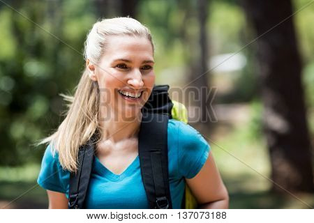 Portrait of a woman smiling with a backpack on the wood