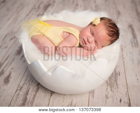 funny sleeping baby in yellow romper with chicken toy on round cot, top, view