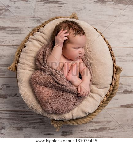wrapped sleepy baby with folded legs and hands on head, top view