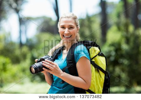 Woman smiling and posing with her camera on the wood