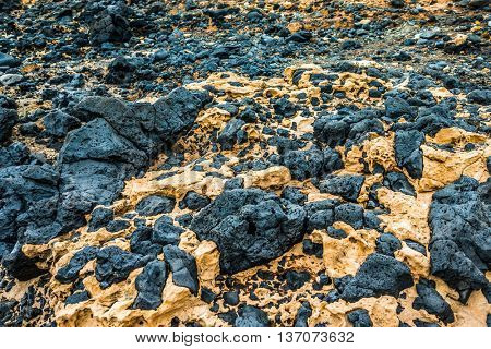 black stones from hardened volcanic lava in Lanzarote, Spain