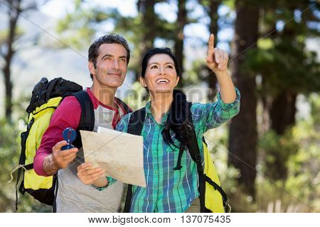 Couple pointing and holding a map on the wood