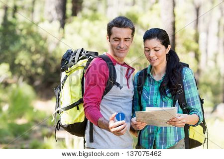 Couple studying a map and a compass on the wood