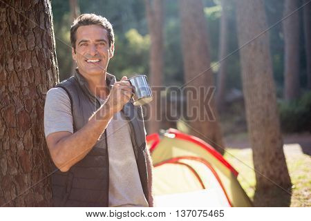 Man smiling and holding cup on a camp site