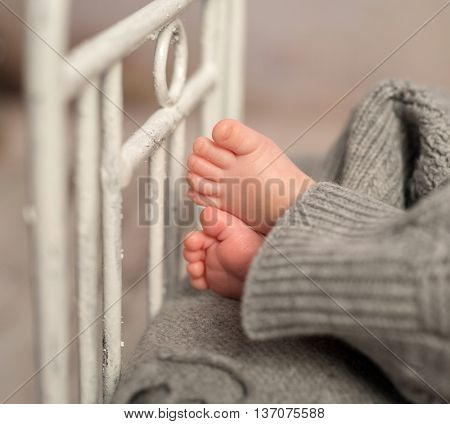 funny bare baby feet out of gray pants on old cot with headboard, closeup