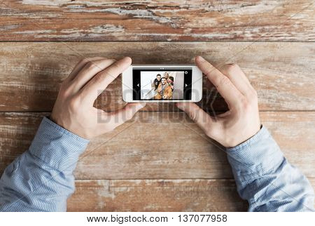 people, memory, relations and technology concept - close up of male hands holding smartphone with photo of happy friends on screen at table poster