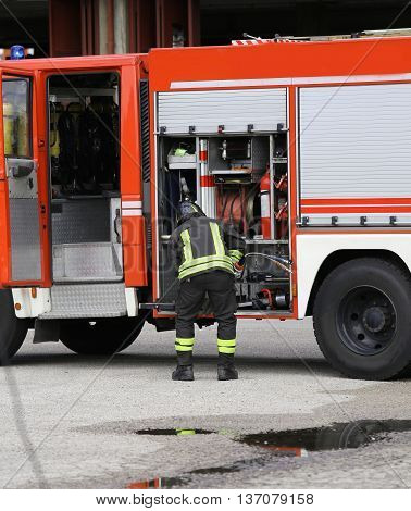 Firefighter Prepares The Water Hoses To Put Out The Fire