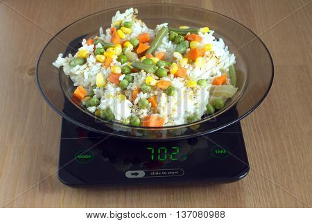 Translucent white plate with rice and vegetables is at home kitchen electronics scales to count calories in food on wooden table. Photo closeup