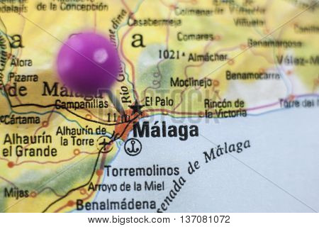 Pushpin marking on Malaga Spain. Selective focus on city poster